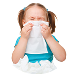 Little girl sneezing into a tissue